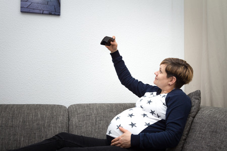 Pregnant woman sitting on a sofa and making a selfie Standard-Bild