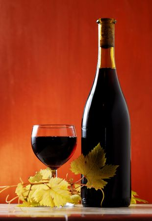 wine bottle and glass isolated on red