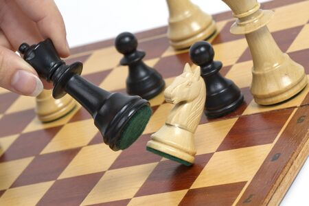 chess board: Picture shows a chess game  The horse is hitting by queen  Studio light  Stock Photo