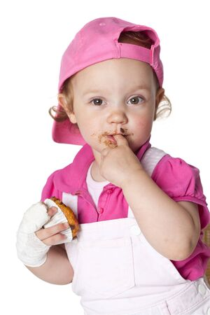 finger licking: Little fashion girl is eating a muffin.