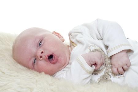 tosiendo: Bebé en un bebé de piel de oveja es de tres meses de edad Studiolight con fondo blanco Foto de archivo
