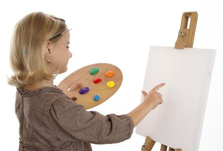 Little girl is preparing canvas for painting  Foto de archivo