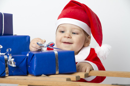 Photo shows in a baby in Santa Claus uniform  In front are blue presents  Studio light with white   photo