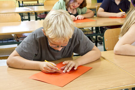 Children during a lesson in a school  Boy is writing something on a red paper   photo
