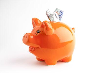 Euros in a orange piggy bank photo