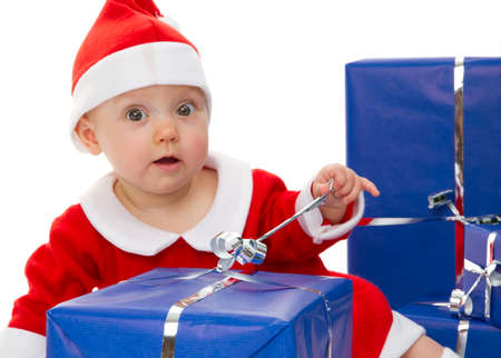 Little baby is wearing Santa Claus outfit  She is preparing christmas gifts   photo