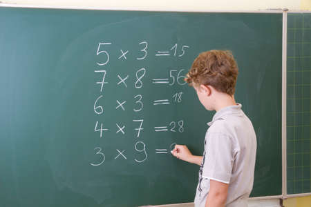 orthographic symbol: Little boy is doing some maths at a blackboard in school