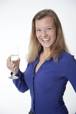A beautiful woman in a blue shirt is holding a glass of wine while Foto de archivo