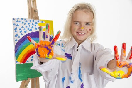 a white robe: Little girl in a white robe painted a rainbow