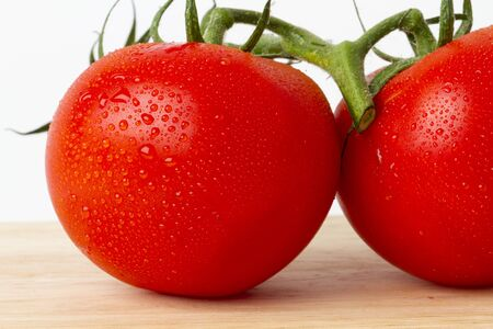 Photo shows two red tomatos on a board. Studio light with soft shadow and white background