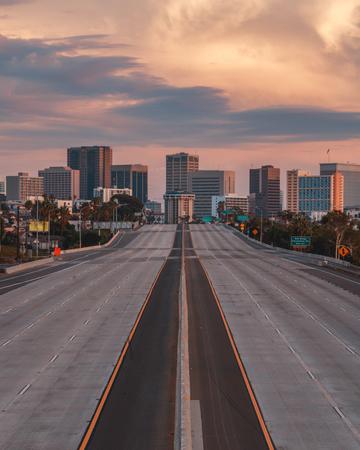 Vista verticale di San Diego, California, USA Skyline con autostrada vuota in primo piano. L'autostrada 5 percorre gran parte della costa degli Stati Uniti occidentali e inizia a San Diego prima di dirigersi verso il Messico.