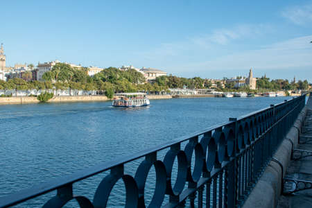 Seville, Spain - November 15, 2019: Romantic river cruise with the golden tower in the background