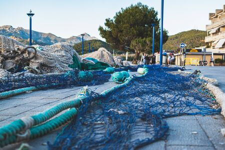Fishing nets in port blue and green color when not in use stacked together for renovation Stock Photo
