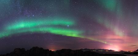 Aurora borealis above the mountains with milky way at Lofoten - Norway