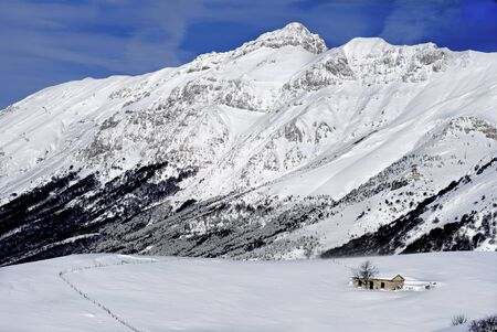 apennines: winter landscape with hut and blue sky
