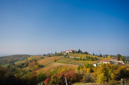 green hills and the red and yellow tones typical of the Piedmontese Langhe in autumn and with a cobalt blue sky