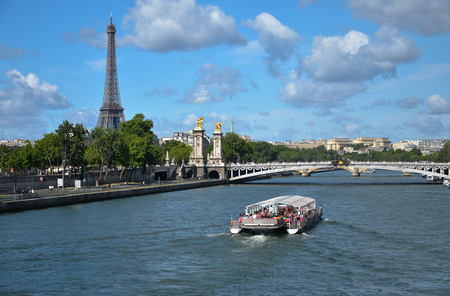 a bateaux mouches on the Seine sails under the third alexander bridge of Paris and in the background the Tour Eiffel