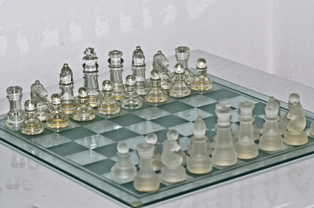 Transparent and opaque chess on glass chessboard