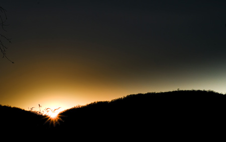 Italian sunset in the hills with the suns rays illuminating everything 写真素材