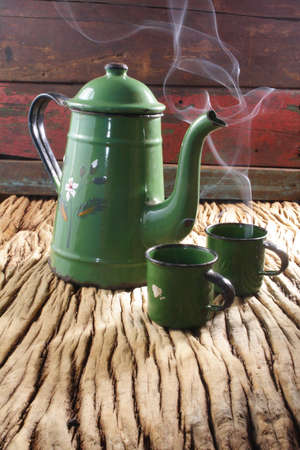 green coffee pot with two cups steaming on wood photo