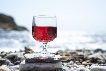 Rosé wine in a glass with the beach and the sea in the background Zdjęcie Seryjne