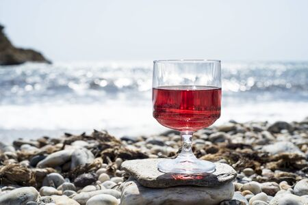 Rosé wine in a glass with the beach and the sea in the background