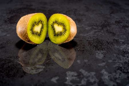 Creative pictures of fresh kiwis on slate and black background