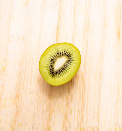 Fresh and juicy kiwi cut on white background, bamboo and slate
