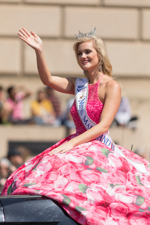 Washington, D.C., USA - April 14, 2018 Miss Maryland wearing a pink dress with pictures of cherry flowers on a car going down the road in the 2018 National Cherry Blossom Parade