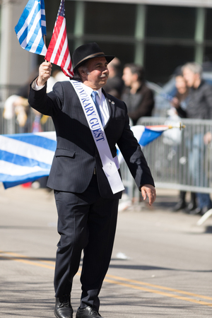 Chicago, Illinois, USA - April 29, 2018 Man carrying the american and greek flags with a ribbon that says honorary guest at the Greek Independence  Day Parade