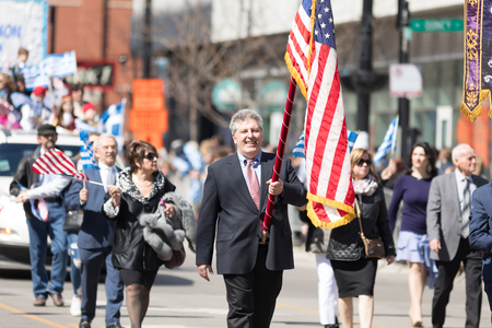 Chicago, Illinois, USA - April 29, 2018  Greek man carrying the USA flag during the Greek Independence  Day Parade