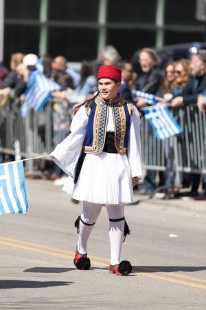 Chicago, Illinois, USA - April 29, 2018  Greek child wearing traditional clothing waving the greek flag during the Greek Independence  Day Parade Standard-Bild - 107044698