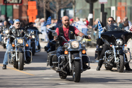 Chicago, Illinois, USA - April 29, 2018 Greek bikers carrying greek and american flags at the Greek Independence  Day Parade Standard-Bild - 107044702