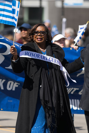 Chicago, Illinois, USA - April 29, 2018  Woman waving the greek flag with a ribon that says honorary guest during the Greek Independence  Day Parade
