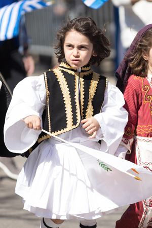 Chicago, Illinois, USA - April 29, 2018  Greek Child wearing traditional clothing waving a flag during the Greek Independence  Day Parade Standard-Bild - 107044707