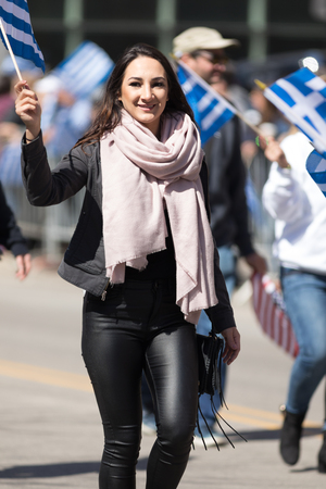 Chicago, Illinois, USA - April 29, 2018 Young greek woman waving the greek flag during the  Greek Independence  Day Parade Standard-Bild - 107044709