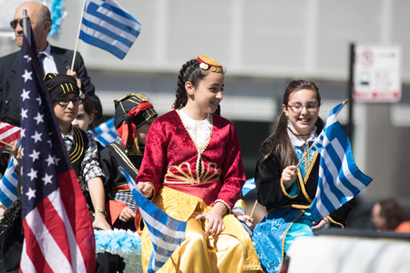 Chicago, Illinois, USA - April 29, 2018 Greek Children wearing traditional clothing waving the greek and usa flag during the Greek Independence  Day Parade Standard-Bild - 107044710
