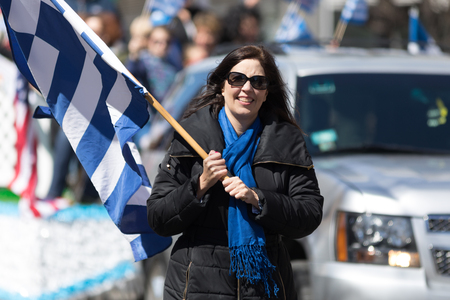 Chicago, Illinois, USA - April 29, 2018 greek woman carrying the greek flag during the Greek Independence  Day Parade Editorial
