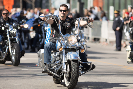 Chicago, Illinois, USA - April 29, 2018 Greek bikers carrying greek and american flags at the Greek Independence  Day Parade Standard-Bild - 106862637