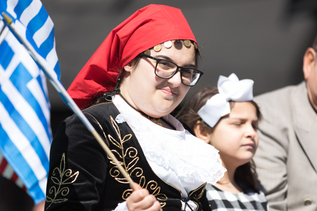 Chicago, Illinois, USA - April 29, 2018  Woman wearing traditional clothing waving the greek flag Greek Independence  Day Parade Standard-Bild - 106862638