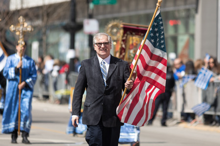 Chicago, Illinois, USA - April 29, 2018  Greek man  carrying the USA flag during the Greek Independence  Day Parade Standard-Bild - 106862642