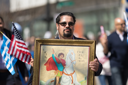 Chicago, Illinois, USA - April 29, 2018  Greek man carrying a painting of St. George from the Greek Orthodox Church during the Greek Independence  Day Parade Standard-Bild - 106862645