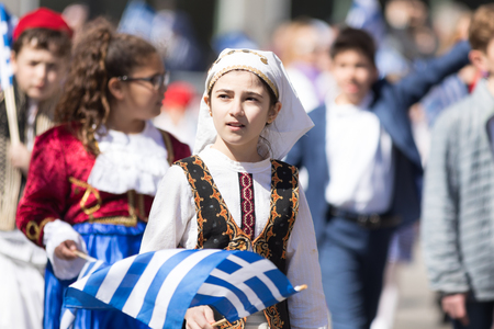 Chicago, Illinois, USA - April 29, 2018  Greek Children wearing traditional clothing and waving greek flags during the Greek Independence  Day Parade Standard-Bild - 106862574