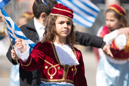 Chicago, Illinois, USA - April 29, 2018  Greek Children wearing traditional clothing and waving greek flags during the Greek Independence  Day Parade Standard-Bild - 106862576