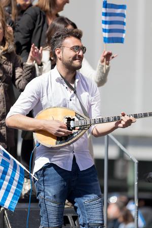 Chicago, Illinois, USA - April 29, 2018 Greek man playing Baglamas during the  Greek Independence  Day Parade Standard-Bild - 106862581