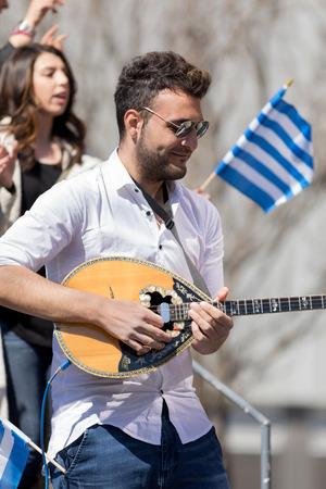 Chicago, Illinois, USA - April 29, 2018 Greek man playing Baglamas during the  Greek Independence  Day Parade Standard-Bild - 106862583