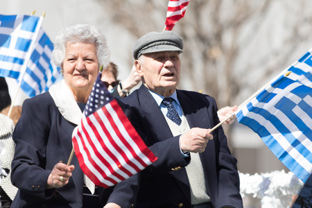 Chicago, Illinois, USA - April 29, 2018 Older Greek couple wave the USA and Greek flags during the Greek Independence  Day Parade Standard-Bild - 106862585