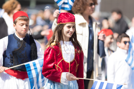 Chicago, Illinois, USA - April 29, 2018 Members of a greek school wearing traditional clothing and waving greek flags during the Greek Independence  Day Parade Standard-Bild - 106862589