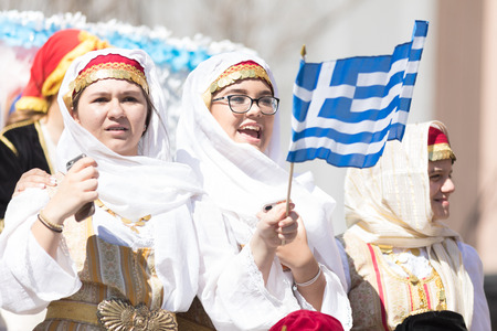Chicago, Illinois, USA - April 29, 2018 Women wearing traditional clothing waving the greek flag during the  Greek Independence  Day Parade