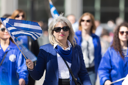 Chicago, Illinois, USA - April 29, 2018 Greek woman waving the greek flag during the Greek Independence  Day Parade Standard-Bild - 106862596